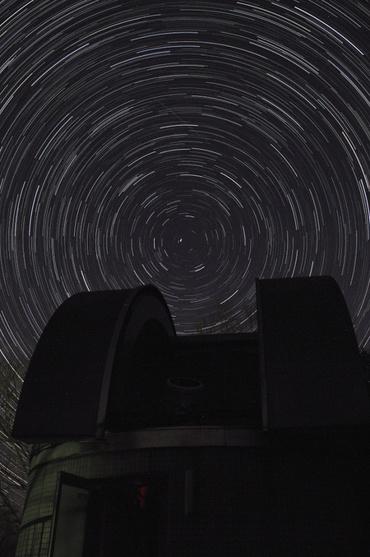 天文台の上を巡る星々と流星